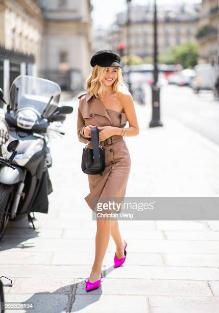 Xenia Adonts wearing flat cap trench coat pink pointed shoes is seen outside Jean Paul Gaultier on day four during Paris Fashion Week Haute Couture...