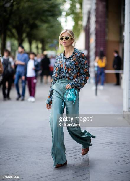 Xenia Adonts wearing high waisted flared mint pants mini bag blouse with floral print is seen outside Acne on day two of Paris Fashion Week Menswear...
