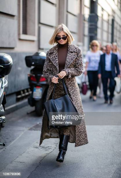 Xenia Adonts wearing leopard print coat and pants black boots brown turtleneck is seen outside Max Mara during Milan Fashion Week Spring/Summer 2019...