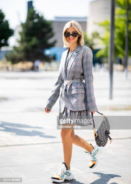 Xenia Adonts wearing Louis Vuitton sneakers, Dior saddle bag, grey checked belted jacket is seen outside Designers Remix during the Copenhagen...