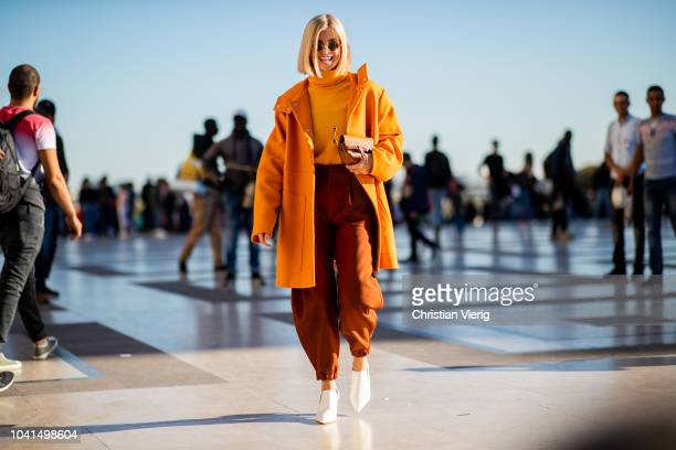 Xenia Adonts wearing orange coat cropped pants white heels is seen outside Rochas during Paris Fashion Week Womenswear Spring/Summer 2019 on...