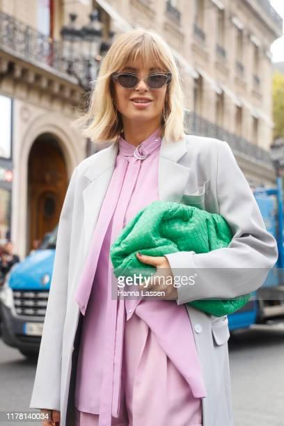 Xenia Adonts wearing pastel pink top and pants, green Bottega Veneta bag outside Stella McCartney during Paris Fashion Week Womenswear Spring Summer...