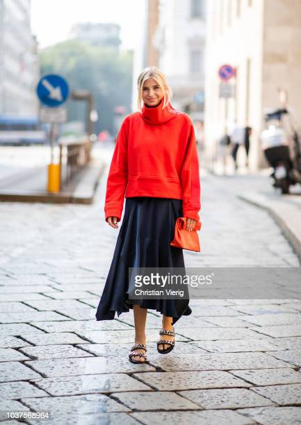 Xenia Adonts wearing red turtleneck red clutch black asymmetric skirt sandals is seen outside Sportmax during Milan Fashion Week Spring/Summer 2019...
