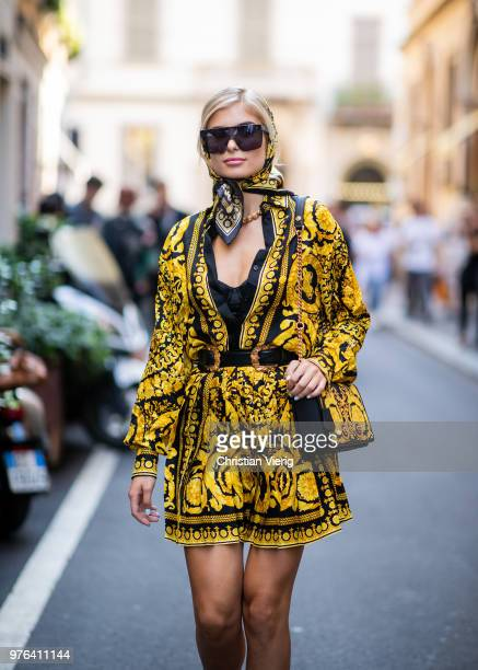 Xenia Adonts wearing scarf around her head Versace skirt and button shirt is seen outside Versace during Milan Men's Fashion Week Spring/Summer 2019...