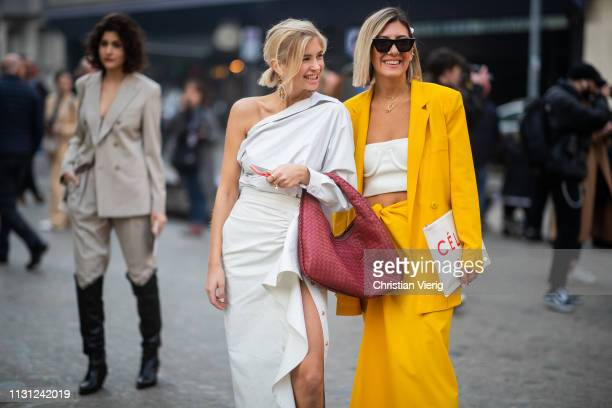 Xenia Adonts wearing white ripped off top skirt with slit and Aylin Koenig is seen wearing yellow blazer skirt white cropped top Celine clutch...