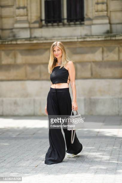 Xenia Adonts wears a beaded necklace with a mini blue teddy bear, a black back-nude sleeveless off-shoulder cropped tank top from Paloma, wide leg...