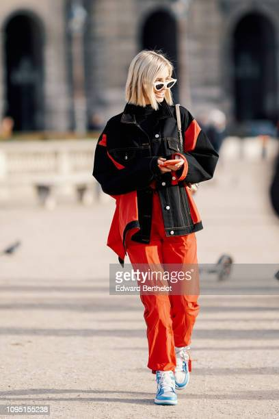 Xenia Adonts wears a black and red denim jacket red pants sunglasses outside OffWhite during Paris Fashion Week Menswear F/W 20192020 on January 16...