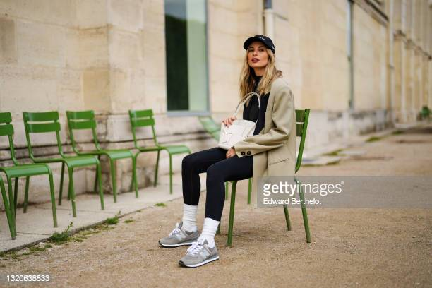 Xenia Adonts wears a black cap from Museum of Peace and Quiet, a black ribbed turtleneck pullover, a beige long oversized jacket from Attire The...