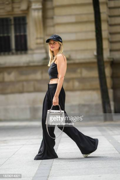 Xenia Adonts wears a black cap from The Museum of Peace and Quiet, a black back-nude sleeveless off-shoulder cropped tank top from Paloma, wide leg...