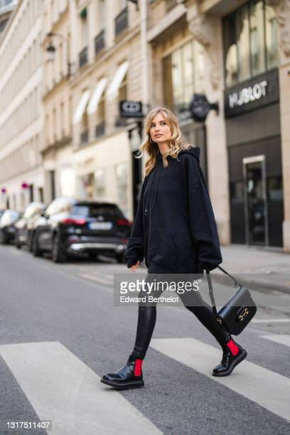 Xenia Adonts wears a black oversized hoodie sweater from Balenciaga, a black leather Gucci Horsebit 1955 shoulder bag, black shiny leather leggings,...