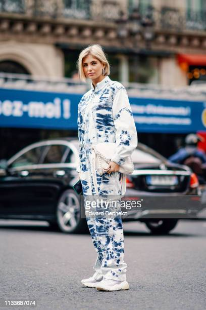 Xenia Adonts wears a blue and white outfit with printed shapes, sneakers a white bag, outside Stella McCartney, during Paris Fashion Week Womenswear...