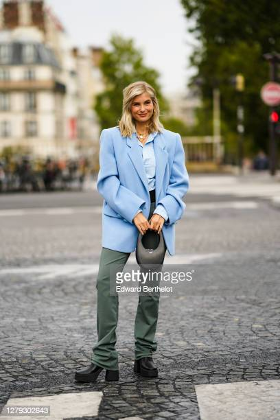 Xenia Adonts wears a blue oversized blazer jacket, a blue shirt, a black bag, green flare pants, black shoes, outside Coperni, during Paris Fashion...