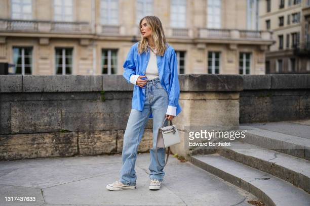 Xenia Adonts wears a blue oversized long shirt with white collar and white cuffs from Attire The Studio, a white ribbed asymmetric top from Attire...