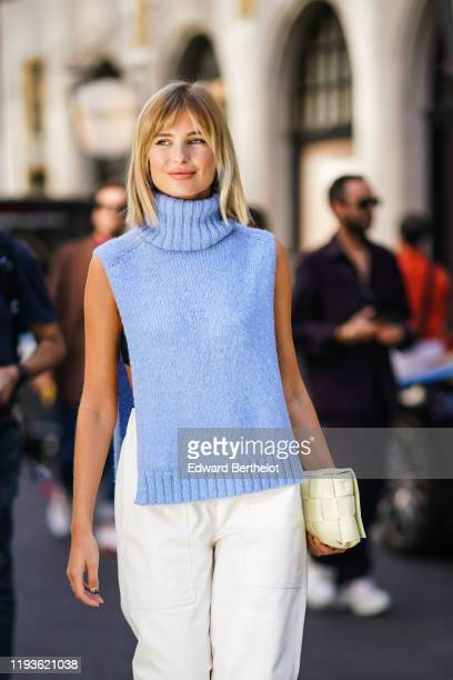 Xenia Adonts wears a blue turtleneck wool sleeveless pullover, white pants, a quilted bag, during London Fashion Week September 2019 on September 15,...