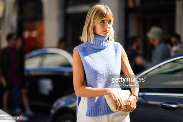 Xenia Adonts wears a blue turtleneck wool sleeveless pullover white pants a quilted bag during London Fashion Week September 2019 on September 15...
