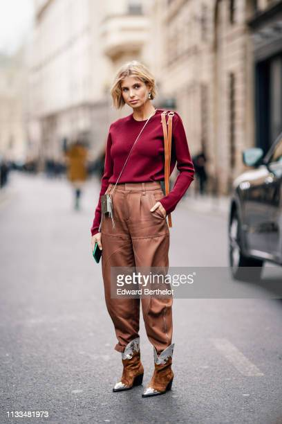 Xenia Adonts wears a burgundy top brown pants brown suede boots a bag earrings outside Thom Browne during Paris Fashion Week Womenswear Fall/Winter...