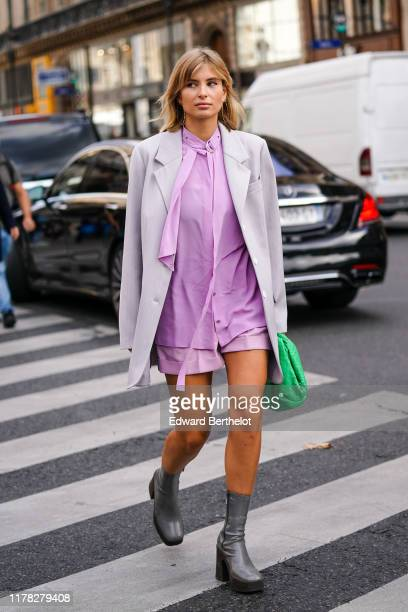 Xenia Adonts wears a gray blazer jacket, a pale pink shirt, a green bag, shorts, gray leather boots, outside Stella McCartney , during Paris Fashion...