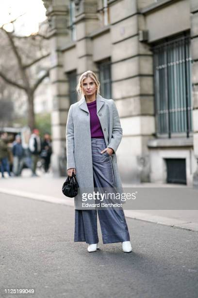 Xenia Adonts wears a gray coat, a purple top, flare pants, white sneakers, a black bag, outside Ralph & Russo during Paris Fashion Week - Haute...