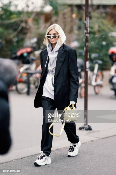 Xenia Adonts wears a gray hoodie sweater, a black blazer jacket, a yellow bag, outside Acne Studios, during Paris Fashion Week Menswear F/W...