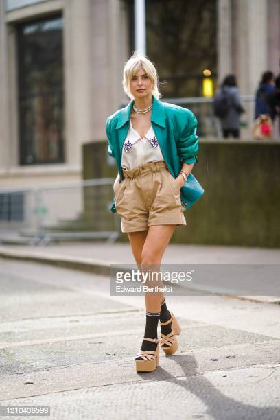 Xenia Adonts wears a green leather jacket with shoulder pads, a low neck shirt with printed flowers on the collar, pale brown shorts, black socks,...
