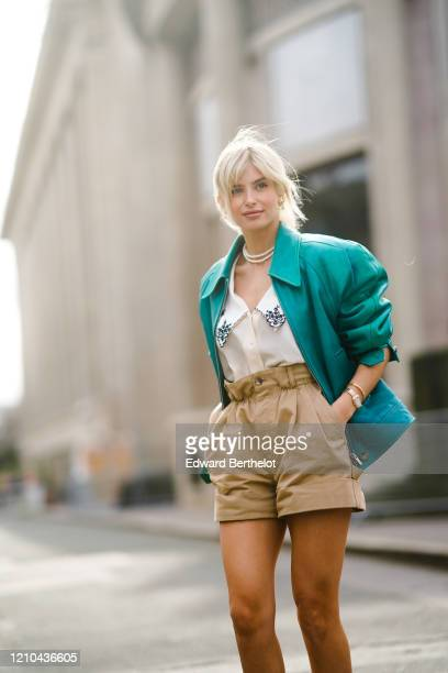 Xenia Adonts wears a green leather jacket with shoulder pads, a low neck shirt with printed flowers on the collar, pale brown shorts, a necklace,...