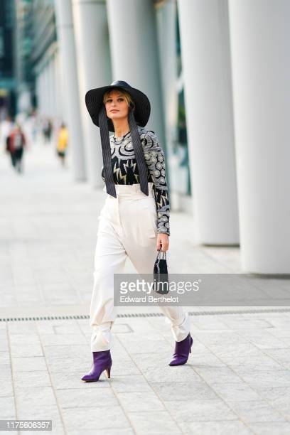 Xenia Adonts wears a hat a top with printed patterns white pants a bag purple shoes outside the Alberta Ferretti show during Milan Fashion Week...