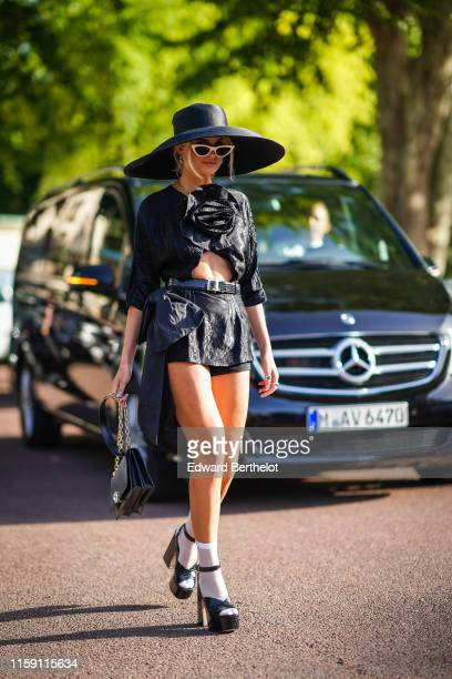 Xenia Adonts wears a large oversized hat, sunglasses, a black dress with attached flower, a belt, a black bag, white socks, black shoes, outside Miu...