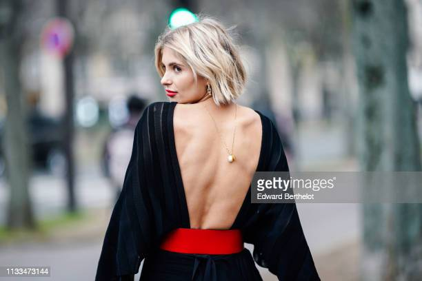 Xenia Adonts wears a necklace a lustrous backless black dress a large red belt outside Valentino during Paris Fashion Week Womenswear Fall/Winter...