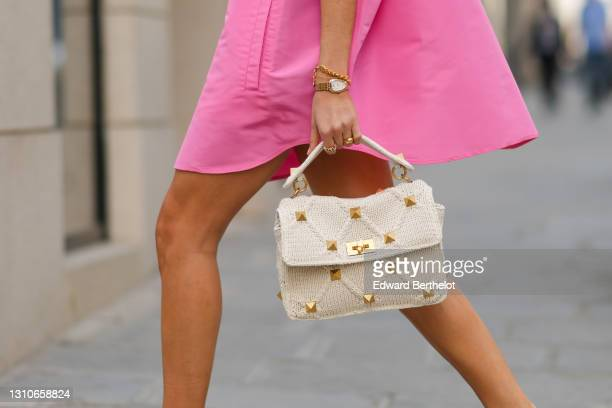 Xenia Adonts wears a neon pink long oversized shirt / dress from Valentino, a white Valentino studded bag, a golden watch, a golden bracelet, during...
