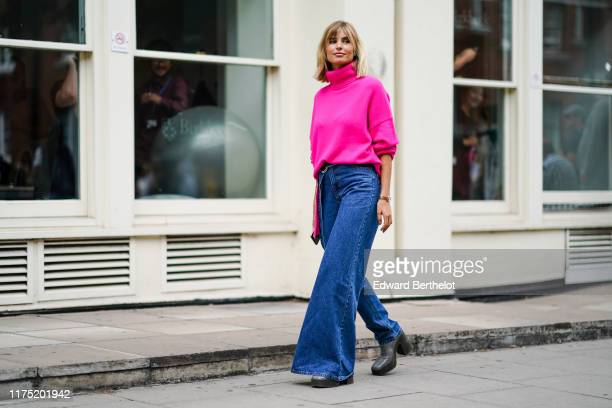 Xenia Adonts wears a neon pink turtleneck wool pullover, blue denim jeans pants with one flare leg, gray platform boots, during London Fashion Week...