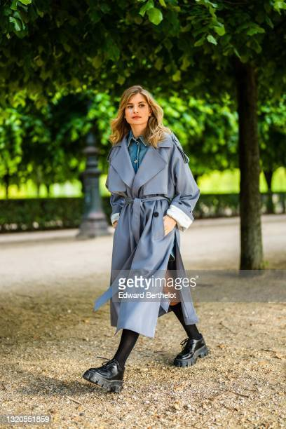 Xenia Adonts wears a Prada blue denim short jumpsuit with buttons, black long socks, black leather Prada shoes, a gray long trench coat from Attire...