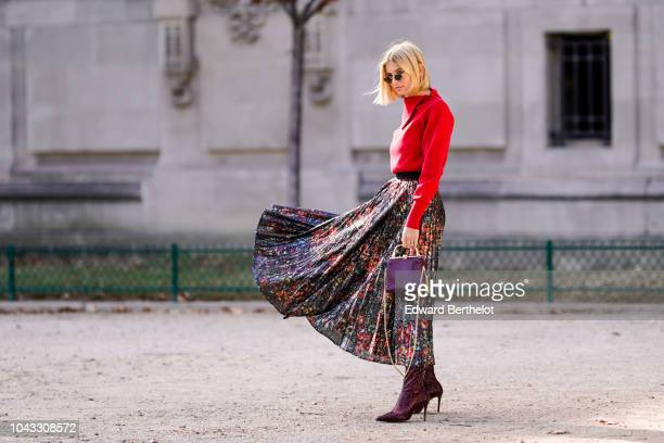 Xenia Adonts wears a red pullover a colored glitter pleated skirt a burgundy leather bag outside Elie Saab during Paris Fashion Week Womenswear...