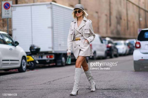 Xenia Adonts wears a white cap, a blazer jacket/dress, a belt with a golden part, a green bag, gray high boots, outside Max Mara, during Milan...
