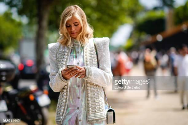 Xenia Adonts wears a white gliter tweed jacket with pearls a white shiny dress outside Balmain during Paris Fashion Week Menswear SpringSummer 2019...