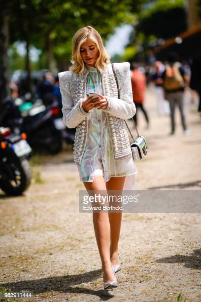 Xenia Adonts wears a white gliter tweed jacket with pearls a white shiny dress outside Balmain during Paris Fashion Week Menswear SpringSummer 2019...