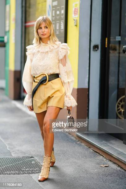 Xenia Adonts wears a white ruffled lace mesh top a leather belt a yellow skirt a Fendi monogram logo brown bag boots outside the Marni show during...