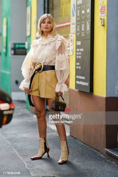 Xenia Adonts wears a white ruffled lace mesh top, a leather belt, a yellow skirt, a Fendi monogram logo brown bag, boots, outside the Marni show...