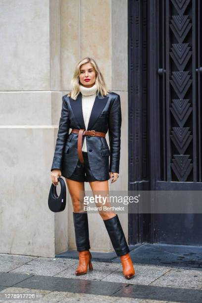 Xenia Adonts wears a white wool turtleneck pullover, a black leather blazer jacket, a brown leather belt, leather shorts, a bag, brown and black...