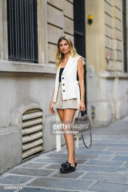 Xenia Adonts wears earrings, a black top, a sleeveless white jacket, gray shorts, a dark gray Hermes Kelly bag, black leather Hermes studded clogs /...