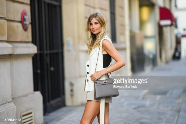 Xenia Adonts wears earrings, a black top, a sleeveless white jacket, gray shorts, a dark gray Hermes Kelly bag, during the Twilly By Hermes : Launch...