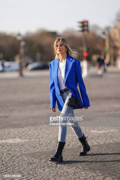 Xenia Adonts wears earrings, a bold blue oversized blazer jacket from Margiela, a white t-shirt from RTA, a black leather pouch bag from Bottega...
