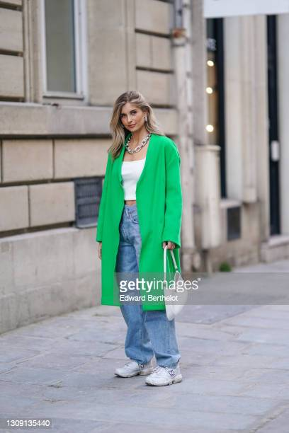 Xenia Adonts wears earrings, a chain metallic necklace, a white ribbed knit cropped tank top, a green long wool winter oversize coat from Dorothee...