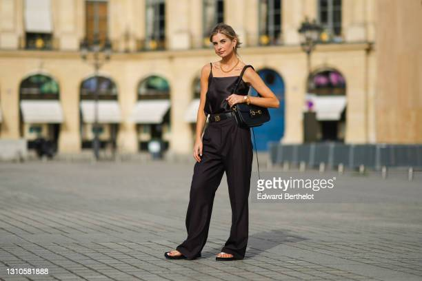 Xenia Adonts wears earrings, a golden necklace, a black silky off-shoulder tank top from Attire The Studio, a Loewe black leather belt with golden...