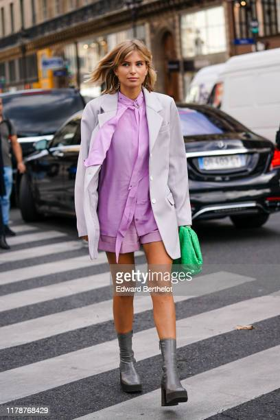 Xenia Adonts wears earrings, a light grey oversized blazer jacket, a light mauve shirt with a lavaliere, shorts, a green woven leather puff clutch,...