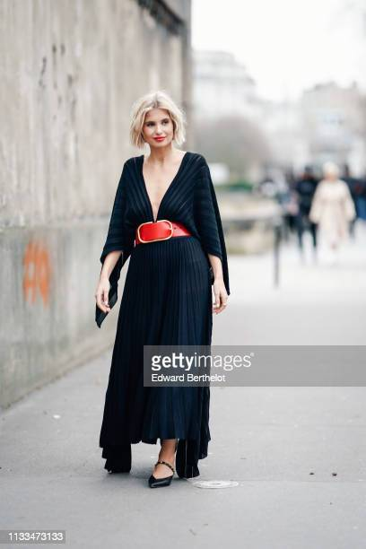 Xenia Adonts wears earrings a lustrous lowcut and pleated asymmetric black dress a large red belt black pointy kittenheeled mules with studded strap...
