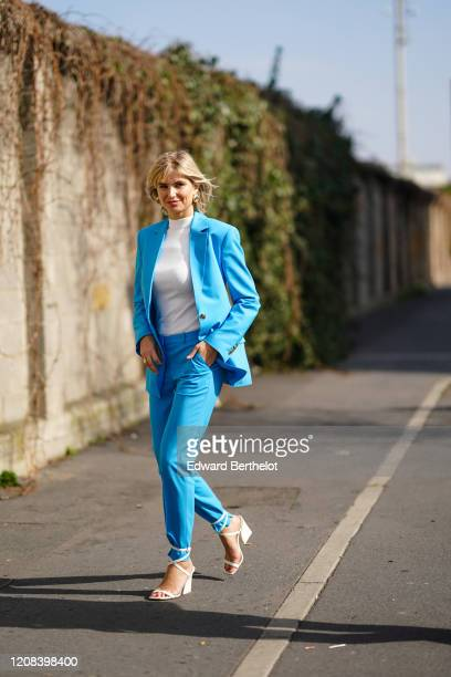 Xenia Adonts wears earrings, a white turtleneck pullover, a blue blazer jacket, blue pants, white shoes, outside BOSS, during Milan Fashion Week...