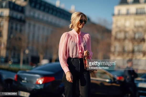 Xenia Adonts wears earrings, sunglasses, a flowing pink top with a bow, black pants, a brown and salmon-color tweed handbag, outside Rochas, during...