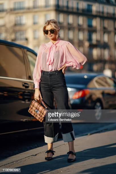 Xenia Adonts wears earrings sunglasses a flowing pink top with a bow black pants a brown and salmoncolor tweed handbag outside Rochas during Paris...
