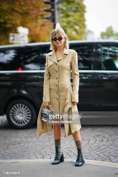 Xenia Adonts wears earrings, sunglasses, a light khaki long sleeves shirt-dress, a Chloe grey and white crocodile pattern bag, black and khaki...