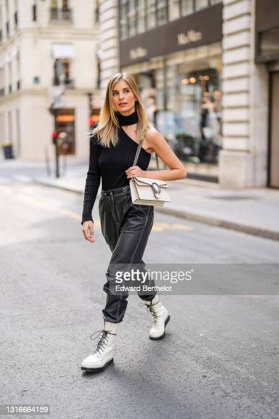 Xenia Adonts wears gold and rhinestones earring, a black wool turtleneck ribs pullover with open neck asymmetrical long sleeve on one side, a white...